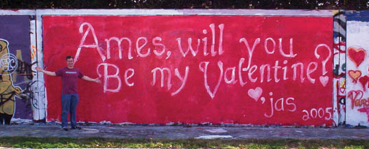 Photos of a man standing in front ofa wall painted in a strong red background with an inviting Valentine message on it.