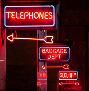 Telephones, Baggage department and Security in capital letters in red neon signs.