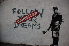 Street art: Follow your dreams, obscured by 'Cancelled' sign