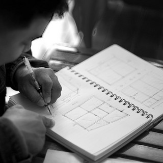 A man sketching notes in a sketchbook