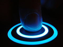 Finger touching a glowing, blue-ringed button