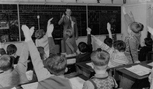 A 1950's era class room with many children with their hands up
