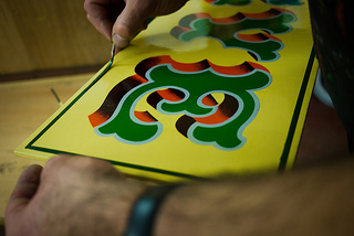 A traditional signwriter creating a classic layered text effect