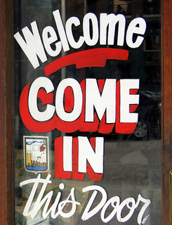 'Welcome. Come in this Door' elegantly painted onto a glass door frame.