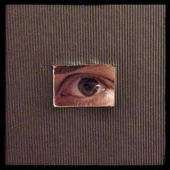 An eye looking through a tiny window