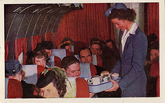 The original onboarding UX - 1950's stewardess serving passengers.