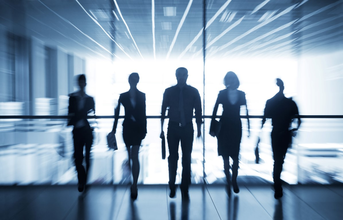 Silhouettes of formally dressed people, blurred, walking towards camera