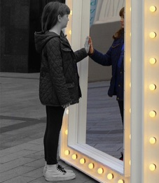 Girl touching a mirror
