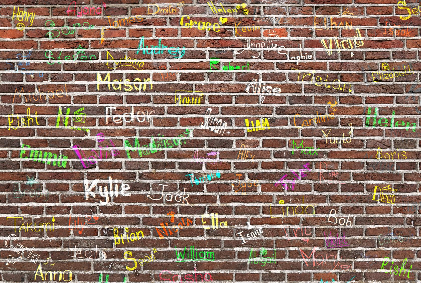 hildren's names written on a brick wall