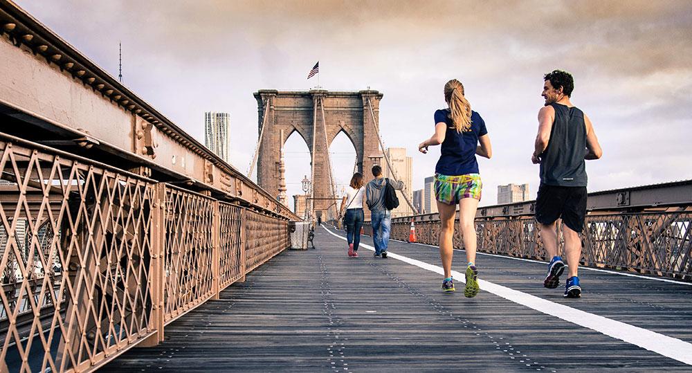 A couple running on a bridge