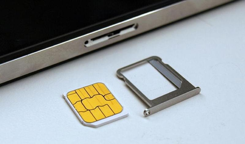 A SIM card and tray, illustrating how the SIM card can only fit one way.