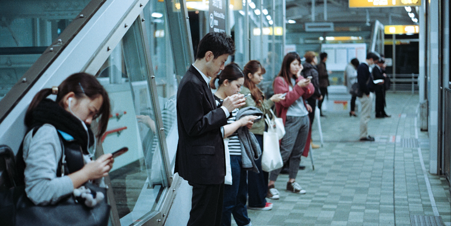 a line of people glued to their mobile phones