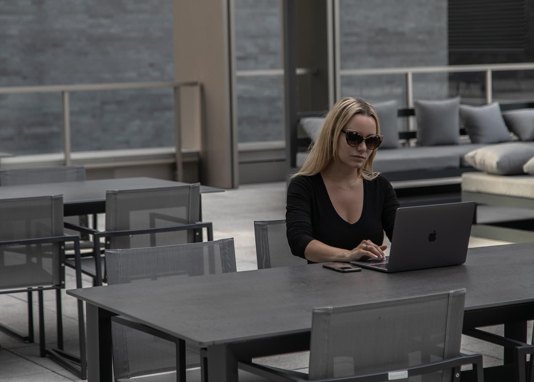 Woman working on laptop at outdoor table